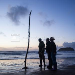 Three People Observe Beach Art