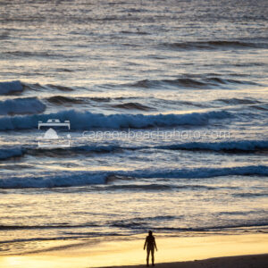 Woman Silhouetted at Sunset on the the Edge of the Pacific